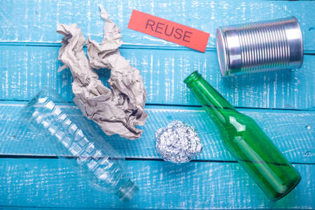 Recycle concept showing waste products of paper, glass, plastic, foil paper & reuse on a blue weathered background Stok Fotoğraf