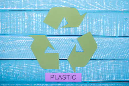 Recycle concept showing the green recycle logo with plastic on a blue weathered background