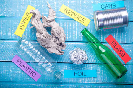 Recycle concept showing waste products of paper, glass, plastic, foil paper & reduce on a blue weathered background