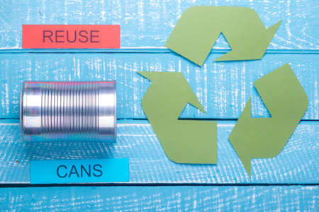 Recycle concept showing green recylce logo with cans on a blue weathered background and reuse