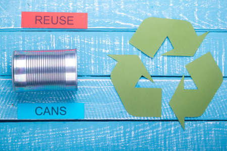 Recycle concept showing cans with the green recycle logo & reuse on a blue weathered background