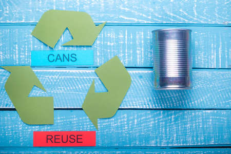 Recycle concept showing the green recycle logo with cans & reuse on a blue weathered background Stok Fotoğraf