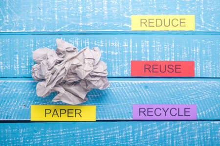 Recycle concept showing paper with reduce, reuse & recycle on a blue weathered background