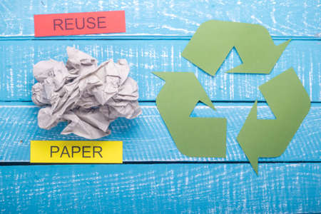 Recycle concept showing paper with the green recycle logo & reuse on a blue weathered background