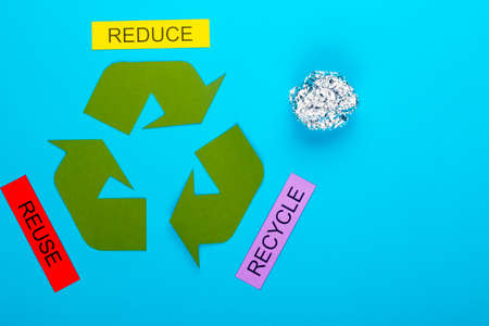 Recycle concept showing the green recycle logo with reduce, reuse, recycle & foil on a blue background