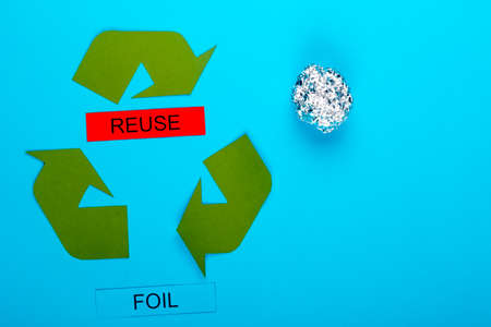 Recycle concept showing the green recycle logo with reuse & foil on a blue background