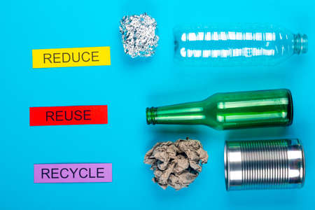 Recycle concept showing glass, foil, cans, paper & plastic on a blue background Imagens