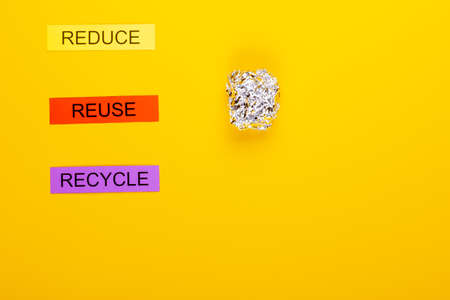 Recycling concept showing reduce, reuse, recycle & foil on a yellow background Stok Fotoğraf
