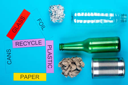 Recycle concept showing glass, foil, cans, paper & plastic on a blue background Stok Fotoğraf