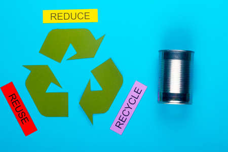 Recycle concept showing the green recycle logo with reduce, reuse, recycle & cans on a blue background