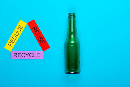 Recycle concept showing reduce, reuse & recycle with glass on a blue background