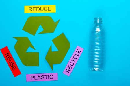 Recycle concept showing the green recycle logo with reduce, reuse, recycle & plastic on a blue background Stok Fotoğraf