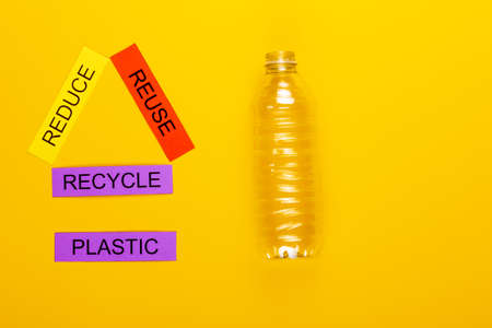 Recycling concept showing reduce, reuse & recycle with plastic on a yellow background Stok Fotoğraf