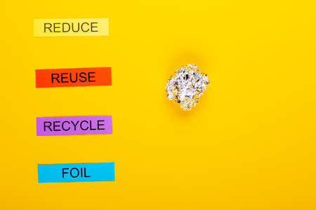Recycling concept showing reduce, reuse, recycle & foil on a yellow background Banco de Imagens