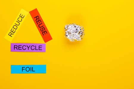 Recycling concept showing reduce, reuse & recycle with foil on a yellow background Stok Fotoğraf