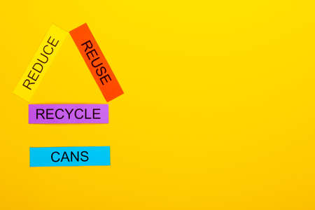 Recycling concept showing reduce, reuse & recycle with cans on a yellow background Stok Fotoğraf