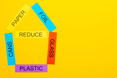 Recycling concept showing paper,foil, cans, glass, paper & reduce on a yellow background Stok Fotoğraf