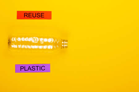 Recycling concept showing reuse & plastic on a yellow background