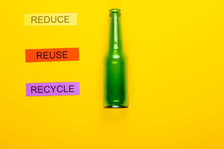 Recycling concept showing reduce, reuse, recycle & glass on a yellow background