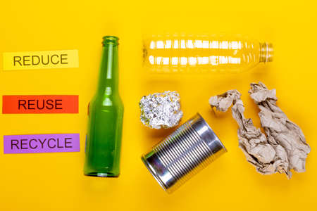 Recycling concept showing paper,foil, cans, glass, paper & reduce, reuse & recycle on a yellow background Stok Fotoğraf