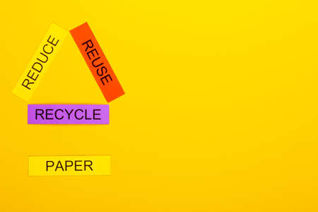 Recycling concept showing reduce, reuse & recycle with paper on a yellow background