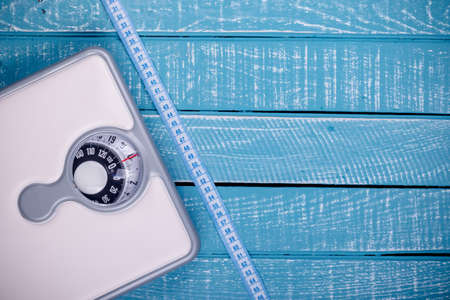 Weight loss concept showing a bathroom scales and a tape measure