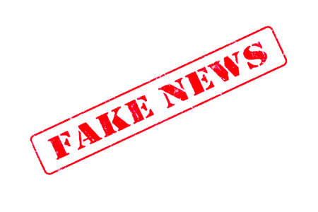 Rubber stamp concept showing a red stamp reading Fake News