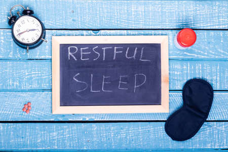 Sleep concept showing an alarm clock, sleeping pills, an  eye mask and a black board reading restful sleep on a weathered blue background Stock Photo