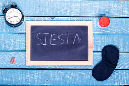 Sleep concept showing an alarm clock, sleeping pills, an  eye mask and a black board reading siesta on a weathered blue background