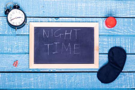 Sleep concept showing an alarm clock, sleeping pills, an  eye mask and a black board reading night time on a weathered blue background
