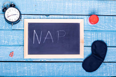 Sleep concept showing an alarm clock, sleeping pills, an  eye mask and a black board reading nap on a weathered blue background