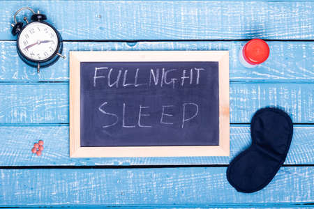 Sleep concept showing an alarm clock, sleeping pills, an  eye mask and a black board reading full night sleep on a weathered blue background
