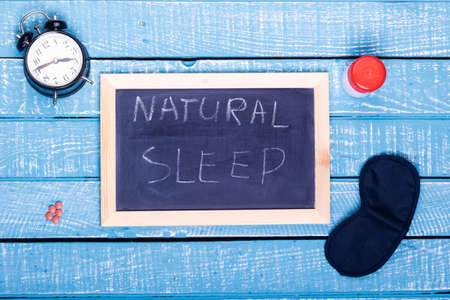 Sleep concept showing an alarm clock, sleeping pills, an  eye mask and a black board reading natural sleep on a weathered blue background
