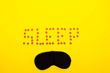 Sleep concept showing sleep spelt in pills with an eye mask on a yellow background