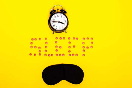Sleep concept showing an eye mask, alarm clock and sleeping pills on a yellow background Stock Photo