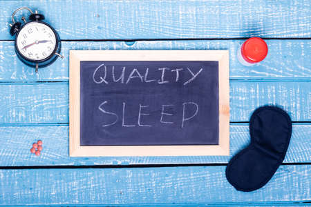 Sleep concept showing an alarm clock, sleeping pills, an  eye mask and a black board reading quality sleep on a weathered blue background