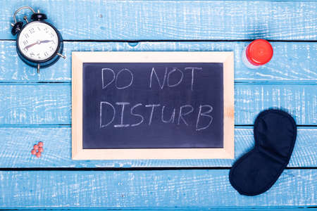 Sleep concept showing an alarm clock, sleeping pills, an  eye mask and a black board reading do not disturb on a weathered blue background