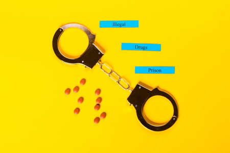Crime concept showing handcuffs on a yellow background with pills and Illegal Drugs Prison