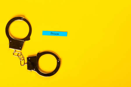 Crime concept showing handcuffs on a yellow background with Prison