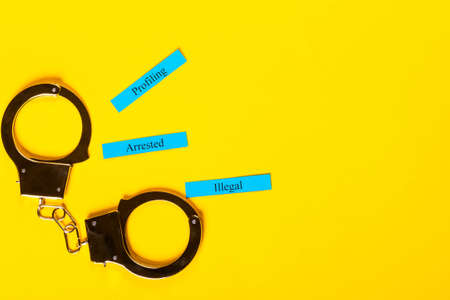 Crime concept showing handcuffs on a yellow background with Profiling Arrested Illegal