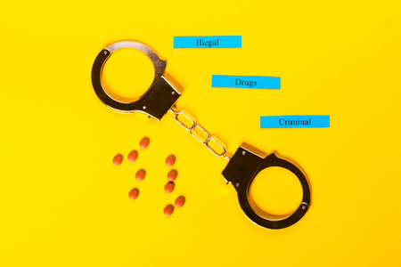 Crime concept showing handcuffs on a yellow background with pills and Illegal Drugs Criminal