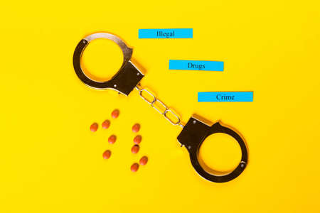 Crime concept showing handcuffs on a yellow background with pills and Illegal Drugs Crime