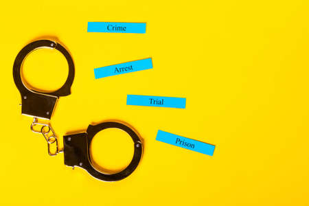 Crime concept showing handcuffs on a yellow background with Arrest Tial Prison Stock Photo - 123313173