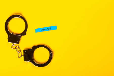Crime concept showing handcuffs on a yellow background with Stock Photo - 123313174
