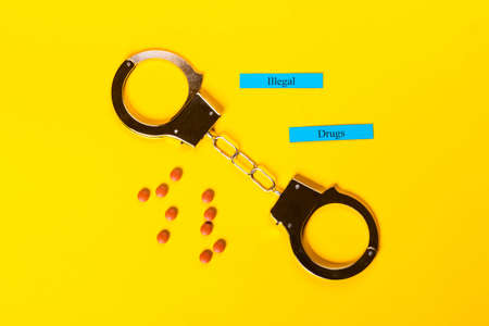 Crime concept showing handcuffs on a yellow background with pills and Illegal Drugs