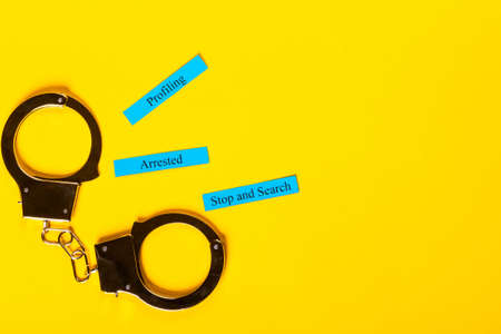 Crime concept showing handcuffs on a yellow background with Profiling Arrested