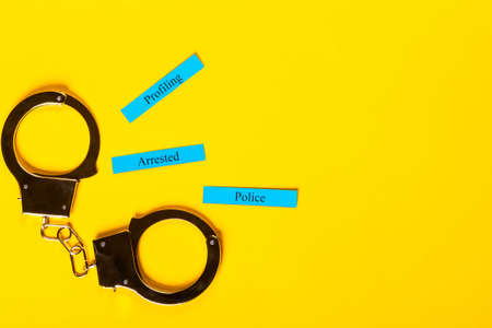 Crime concept showing handcuffs on a yellow background with Profiling Arrested Police Stock Photo