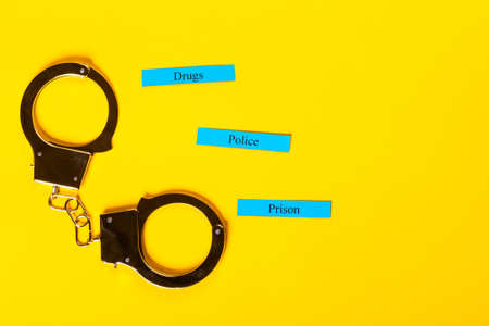 Crime concept showing handcuffs on a yellow background with Police Prison