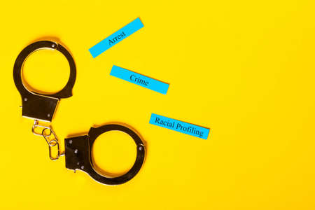 Crime concept showing handcuffs on a yellow background with Racial Profiling 스톡 콘텐츠
