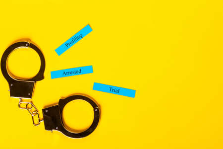 Crime concept showing handcuffs on a yellow background with Profiling Arrested Trial Stock Photo